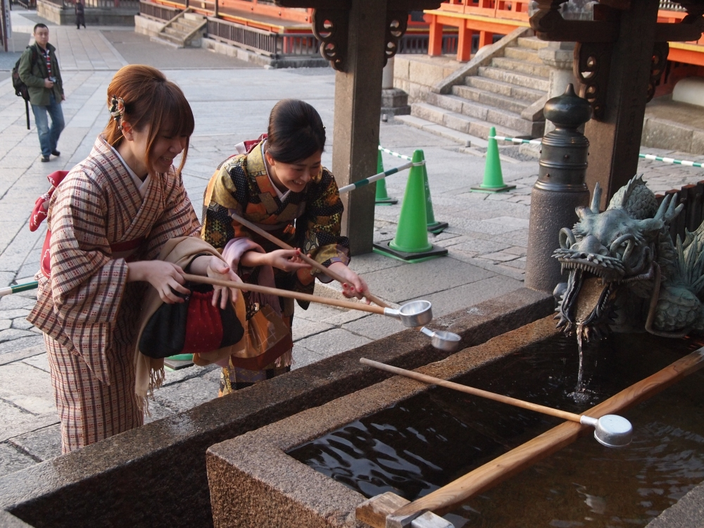 girls in kimono drinking from a well of good fortune at kiyomizu-dera temple